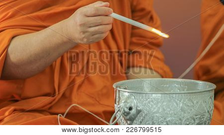 Buddha Monk Hold Candle Above Holy Water Bowl