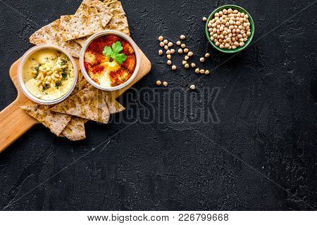 Serve Hummus. Bowl With Dish Near Pieces Of Crispbread On Black Background Top View.