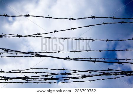 A Barbed Wire. Clouds And Blue Sky.