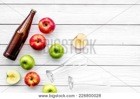 Apple Cider. Low-alcoholic Beveradge In Dark Bottle Near Beer Glasses And Fresh Apples On White Wood