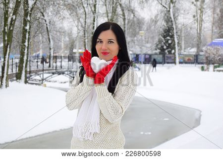 The Young Woman The Brunette Holds A Snowball In The Form Of Heart. The Woman Is Dressed In A White