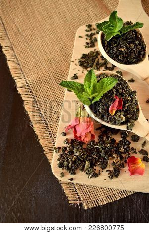 Leaf Tea, Dried Rose And Fresh Mint For Making A Hot Drink On A Wooden Board