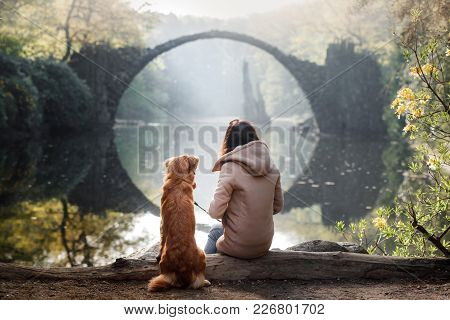 The Girl With The Dog At The Bridge. Nova Scotia Duck Tolling Retriever At The Bridge In The Park