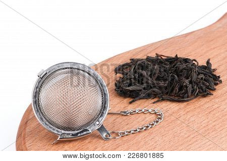 Black Tea, And Tea Strainer With Chain, On Wooden Background. A Black Tea And Tea Strainer Is A Clos