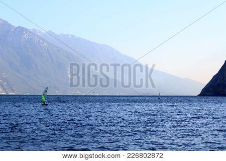 Riva Del Garda, Italy - August 4, 2017: Lake Garda And Mountain Panorama With Boats In Riva. Lake Ga