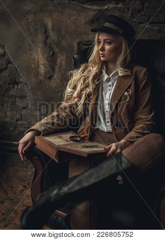 Young Pensive Woman In Image Of Sherlock Holmes Sits In Armchair And Holds Old Photoalbum In Her Han