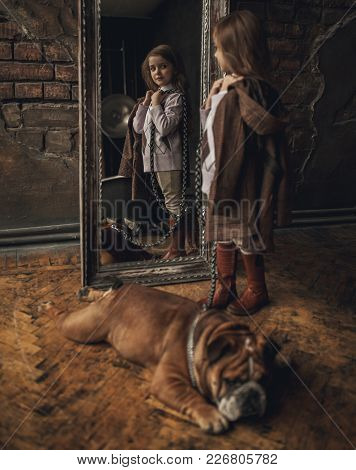 Child Girl In Image Of Sherlock Holmes Stands Next To English Bulldog And Looks At Mirror Reflection