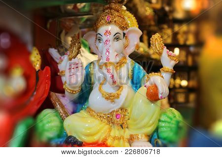 Figurine Of God Ganesha. Indian Souvenir. Beautiful Ganapati With Four Arms Blesses With A Gesture.
