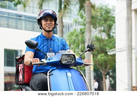 Vietnamese Delivery Man In Helmet Riding On Scooter