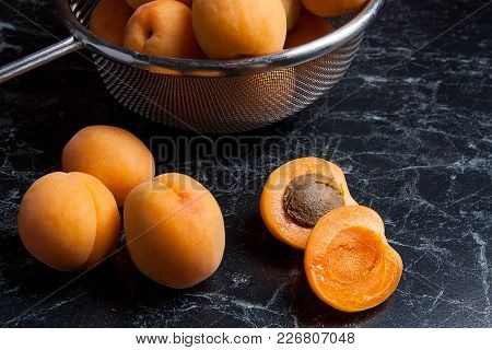 Fresh Organic Apricots In Steel Colander. Group Of Harvested Apricots Whole And Halved In Steel Cola