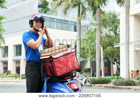 Delivery Man Wearing Helment To Ride On Scooter