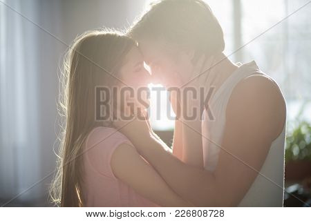 A Portrait Of Two Belovers Standing In The Sunlight. Gently Holding A Girl, A Boy Is Going To Kiss H