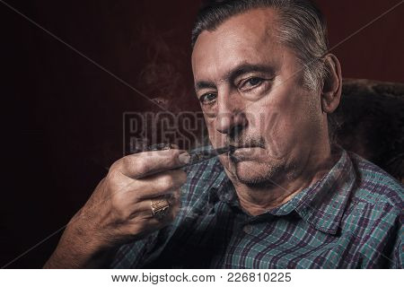 Classy Senior Elderly Man Smoking A Pipe In His Armchair, Red Background