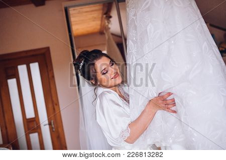Happy Bride In Silk Robe Holding Her Wedding Dress And Smiling. Wedding Morning Preparation.