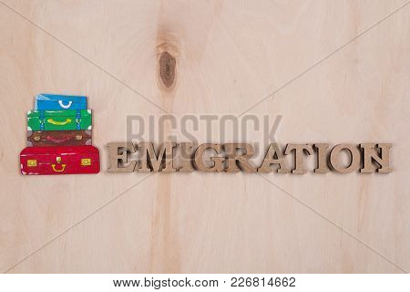 Emmigration, The Word In Abstract Wooden Letters. Background Wooden Surface And A Pile Of Suitcases