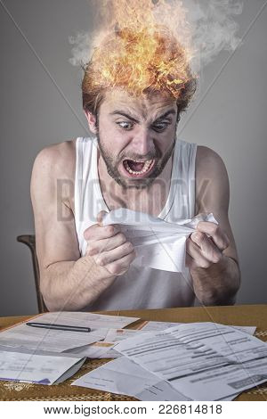 Angry Young Man Tearing His Bills, Furious With The Government And Electricity Companies