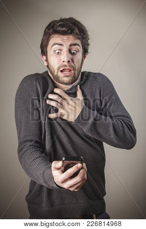 Shocked And Frightened Young Caucasian Man Checking His Phone, Terrified With Its Content