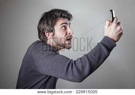 Angry Young Man Shouting At His Cell Phone, Outraged And Appalled