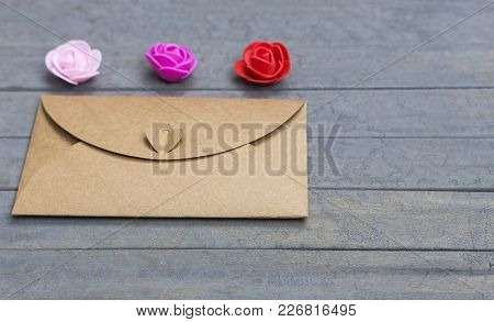 Valentine Day Letter. Envelope From Craft Paper With Heart On It And Three Little Roses Flowers On W