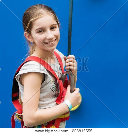 Active little girl in safety climbing harness hangs on rope while practising on climbing wall indoors
