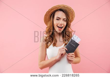 Photo of beautiful woman in white swimsuit and straw hat rejoicing traveling with passport and tickets in hand, isolated over pink background