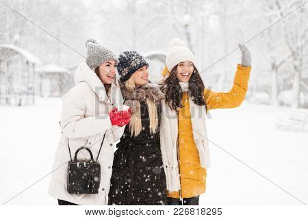 Laughing ladies looking aside and wawing somebody while walking in snow weather in the street