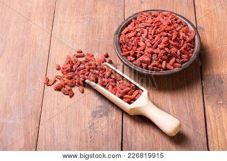 Goji Berries In Wooden Spoon . Superfood Background