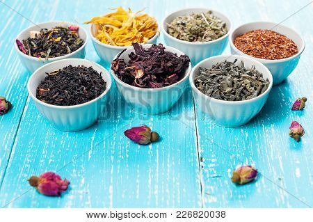Various Dried Medicinal Herbs And Teas In Several Bowls On Blue Wooden Background