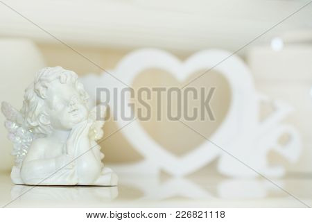 Valentine Day Concept. Statuettes Of Small Angels  Over Light Background