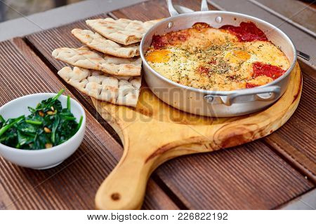 Scrambled Eggs With Tomatoes, Cheese And Spices In An Aluminum Frying Pan With Handles With Homemade