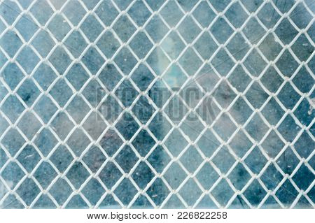 The Textured Background Of A Woven Shallow Mesh Behind A Flashing Glass. Blue Dirty Glass. Vintage C