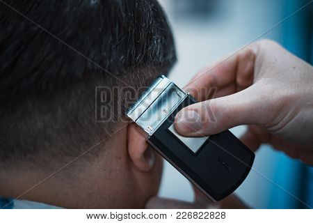 Men's Haircut In Barbershop. Barber Shears Clippers. Close Up. Soft Focus.