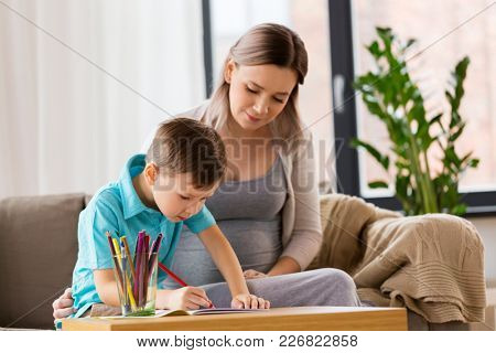 family, education and pregnancy concept - happy pregnant mother and little son with workbook writing or drawing at home