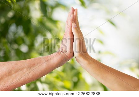 people, age and charity concept - close up of senior and young woman hands touch over green natural background