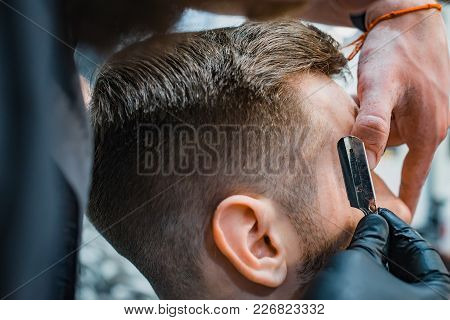 Ideal Shape Of The Beards And Haircuts In Barbershop. Barber Suggests The Outline With A Razor. Men'