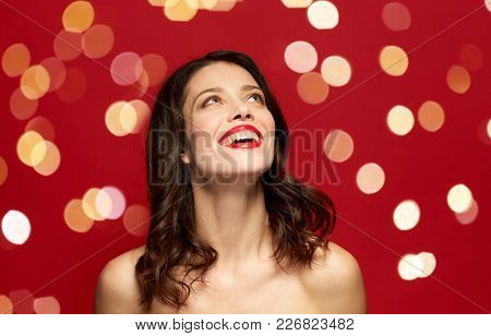 beauty, make up and people concept - happy smiling young woman with red lipstick looking up over holidays lights background