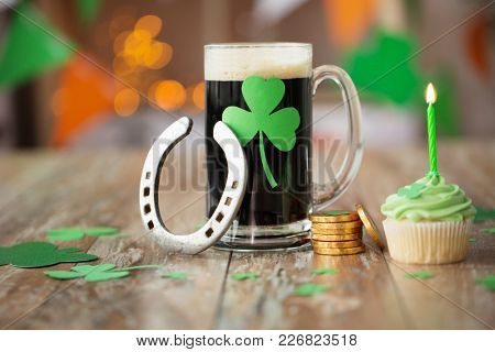 st patricks day, holidays and celebration concept - glass of dark draft beer with shamrock, green cupcake, horseshoe and gold coins on wooden table