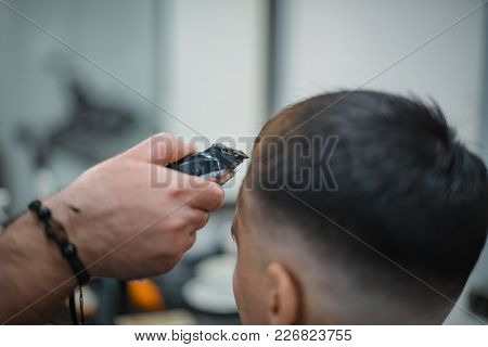 Man Gets A Cool Haircut In Barbershop. Barber Makes The Cut Man Electric Razor. Men's Care Head. Sof