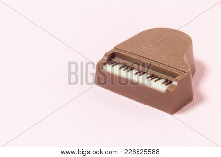 Close Up Of Chocolate Praline Mini Piano Against Pastel Pink Rose Background. Minimal Concept.