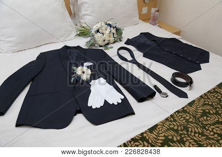 Man Groom Suite, Vest, Tie, Belt, Watch, Bouquet Flower Lying On A Bed For Preparation On Wedding Da