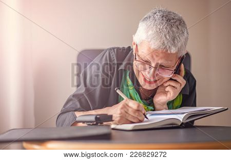 Happy Senior Old Business Woman Writing Down Orders, Talking On Her Cell Phone