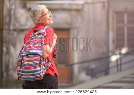 Senior Old Woman Tourist With A Backpack Preparing To Leave Her Home To Go Travelling