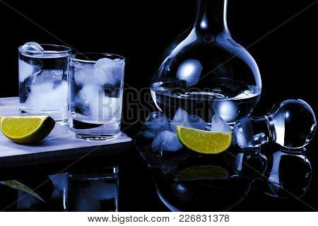 Two Shots Strong Alcohol Near Decanter. Two Shots With Strong Alcohol On A Wooden Board With Ice Cub