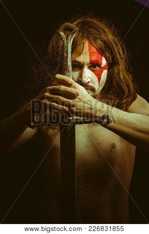 Strong, Wild warrior with metal sword and war paintings on the face, long hair