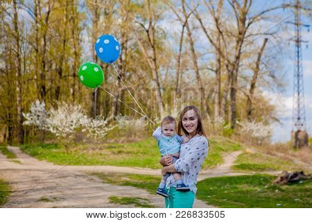 Happy Mom And Baby Hold The Balloons, Mom And Children Have Fun In Summer Nature, Hands Up, Freedom