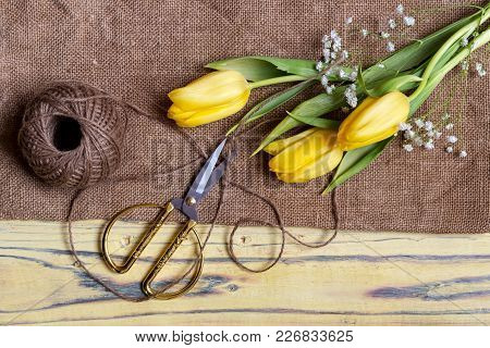 Flower Composition. Delicate, Yellow Tulips And Scissors On A Wooden Table Close-up.