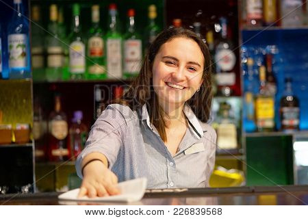 The Girl-bartender Smiles, Wiping The Table With A Rag At The Hotel Bar. Brunette Bartender In The W