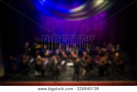 Artists Symphony Orchestra. Abstract Blurred Image. Musician Plays A Musical Instrument On The Conce