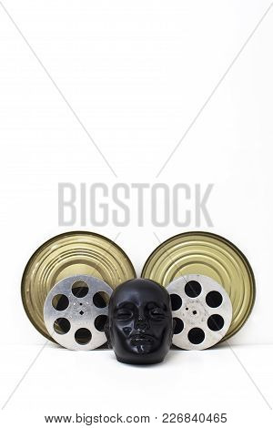 Film Reels Of Old Movies And Black Dummy Head On White.concept Cinema