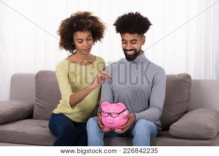 Happy Couple Sitting On Sofa Inserting Coin In Piggybank